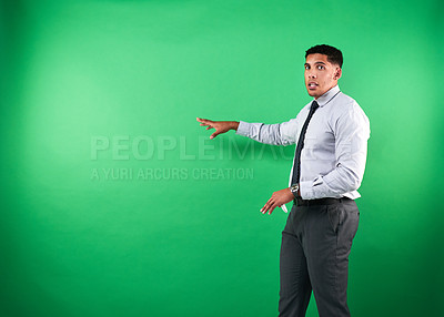 Buy stock photo Cropped portrait of a handsome young male weather forecaster reporting the weather against a green background