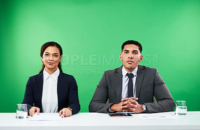 Buy stock photo Cropped shot of two young news anchors smiling while delivering the news against a green background