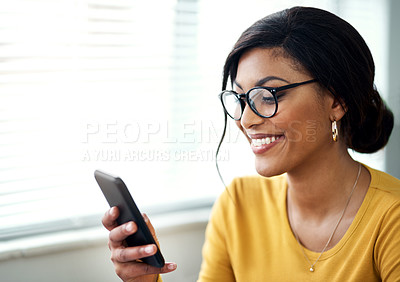 Buy stock photo Cropped shot of an attractive young woman sitting alone and texting on her cellphone in her home