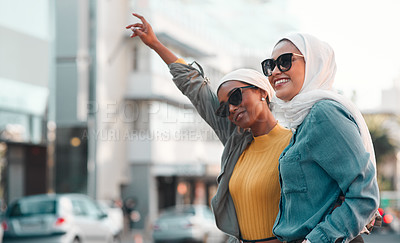 Buy stock photo Cropped shot of two attractive young women wearing sunglasses and headscarves while hailing a taxi in the city