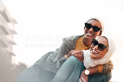 Buy stock photo Cropped shot of an attractive young woman wearing sunglasses and a headscarf while giving her female friend a piggyback ride