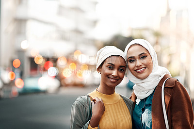 Buy stock photo Cropped shot of two attractive young women wearing headscarves and standing together while touring the city together