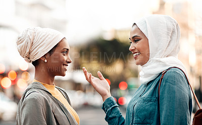 Buy stock photo Cropped shot of an attractive young woman wearing a hijab and talking with her female friend while touring the city
