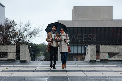 Buy stock photo Cropped shot of a cheerful young couple walking together while holding an umbrella outside in the rain