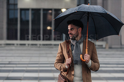 Buy stock photo Cropped shot of a handsome young businessman holding an umbrella while standing in the rain outside during the day