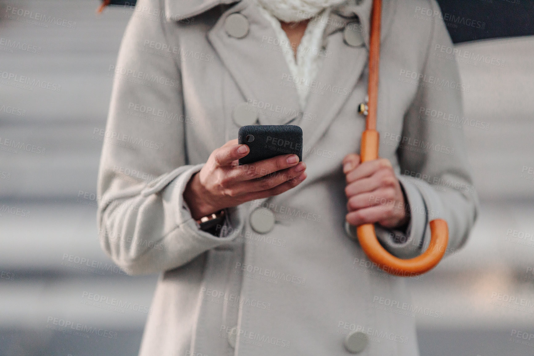 Buy stock photo Cropped shot of an unrecognizable businesswoman texting on her cellphone while holding an umbrella outside in the rain