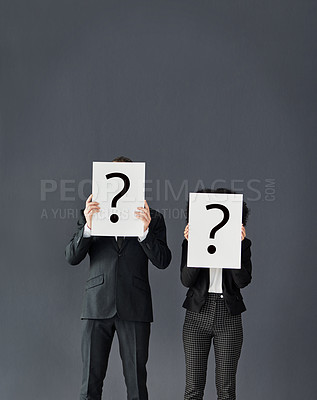 Buy stock photo Studio shot of two unrecognizable businesspeople holding placards with question marks on them against a grey background