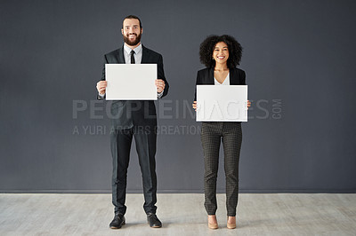 Buy stock photo Full length shot of two young corporate businesspeople holding blank placards against a grey background
