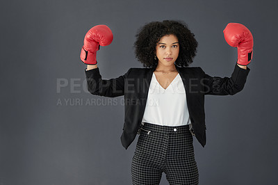 Buy stock photo Studio portrait of a young corporate businesswoman posing wearing boxing gloves against a grey background