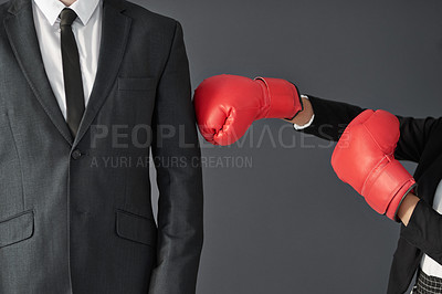 Buy stock photo Shot of an unrecognizable businesswoman wearing boxing gloves punching a businessman against a grey background