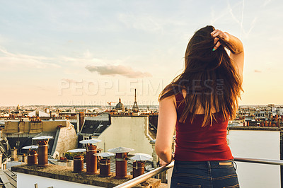 Buy stock photo Rearview shot of a woman standing on a rooftop and looking at the beautiful city of Paris, France at sunset