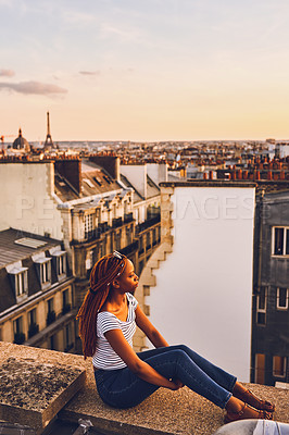 Buy stock photo Full length shot of an attractive young woman sitting on a rooftop and looking at the cityscape in Paris, France