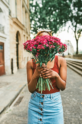 Buy stock photo Shot of an unrecognizable woman holding a bouquet of flowers over her face in the streets of Paris, France
