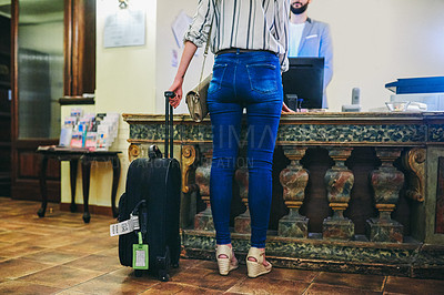 Buy stock photo Rearview shot of an unrecognizable woman holding a suitcase while checking in to a hotel