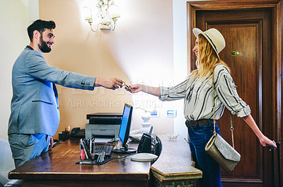 Buy stock photo Cropped shot of a handsome young male receptionist handing over a bunch of keys to a female visitor at the front desk of a hotel
