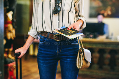 Buy stock photo Cropped shot of an unrecognizable woman holding a suitcase and a passport while standing in front of a hotel reception