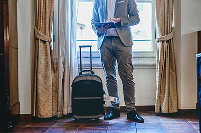 Buy stock photo Cropped shot of an unrecognizable businessman using a digital tablet while standing by his suitcase inside his hotel room