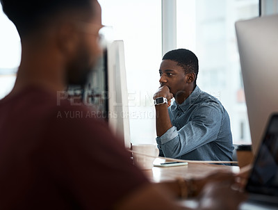 Buy stock photo Shot of a handsome young businessman working on a computer inside a modern office with colleagues in the background