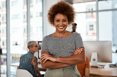 Buy stock photo Portrait of an attractive young businesswoman posing with her arms folded inside an office with her colleagues in the background