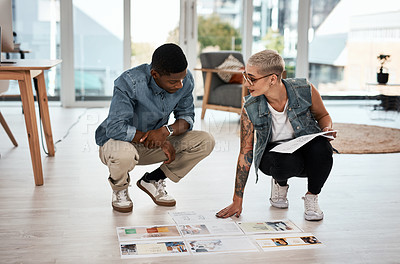 Buy stock photo Full length shot of two young businesspeople going over paperwork and designs on the floor together inside an office