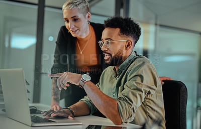 Buy stock photo Shot of two young designers working together on a laptop in an office at night