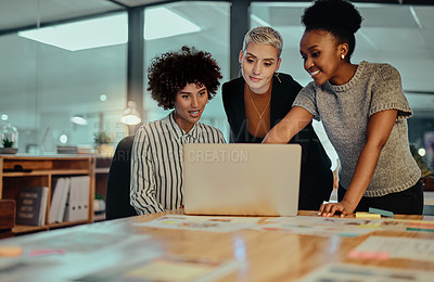Buy stock photo Shot of a group of young businesswomen working together on a laptop in an office at night