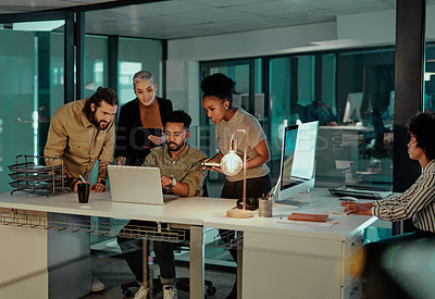 Buy stock photo Shot of a group of young designers working together on a laptop in an office at night