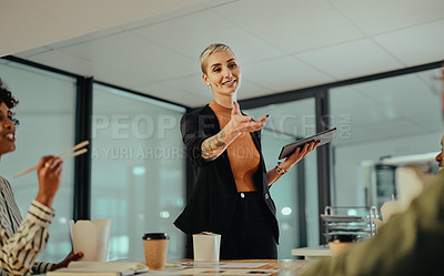 Buy stock photo Shot of a young businesswoman giving her colleagues a presentation in an office at night