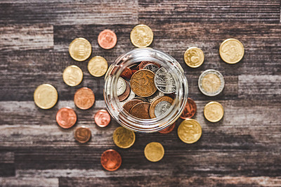 Buy stock photo High angle shot of coins in a jar on a wooden background