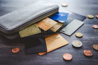 Buy stock photo Shot of multiple bank cards and coins laying on a wooden background