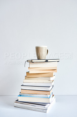 Buy stock photo Shot of a pile of books on a table with a cup of coffee on top