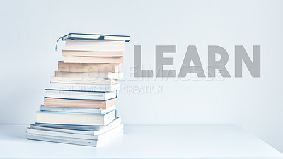 """Buy stock photo Shot of a pile of books stacked up on a table with the word """"learn"""" next to them"""