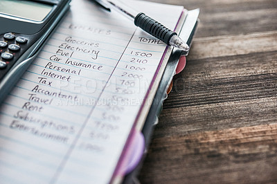 Buy stock photo Shot of a notebook with a budget written on it and a calculator on a desk at home