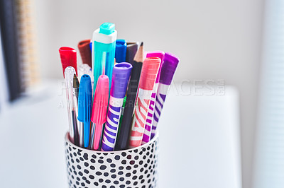 Buy stock photo Shot of various colourful markers in a pen holder on a desk