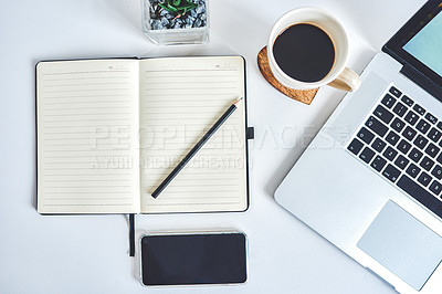 Buy stock photo High angle shot of a laptop, notebook and smartphone on a work desk