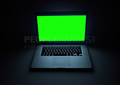 Buy stock photo Shot of a laptop with a green screen on a work desk at night