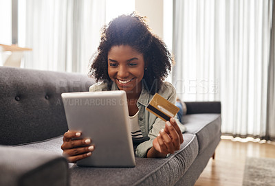 Buy stock photo Shot of a woman holding a credit card while using a digital tablet
