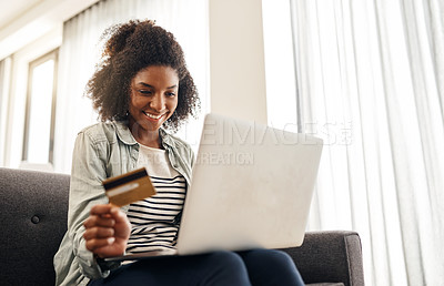 Buy stock photo Shot of a young woman holding her credit card while using her laptop