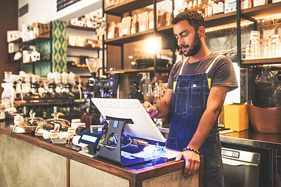 Buy stock photo Shot of a young man using a till in a cafe