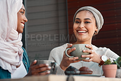 Buy stock photo Cropped shot of two affectionate young girlfriends having coffee with muffins at a coffee shop while dressed in hijab