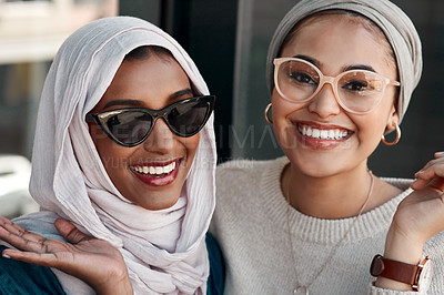 Buy stock photo Cropped portrait of two affectionate young girlfriends hanging out together at a cafe while dressed in hijab