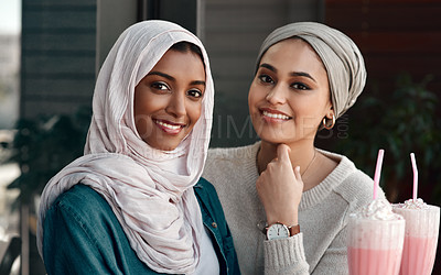 Buy stock photo Cropped portrait of two affectionate young girlfriends hanging out together at a milkshake cafe while dressed in hijab