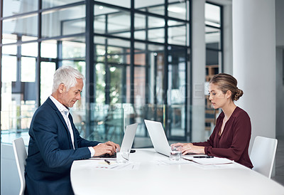 Buy stock photo Shot of a businessman and businesswoman using laptops at a desk in a modern office