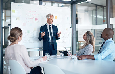 Buy stock photo Shot of a mature businessman delivering a presentation to his colleagues in a modern office