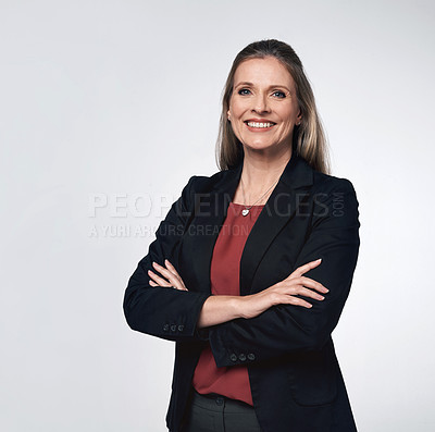 Buy stock photo Portrait of a mature businesswoman standing with her arms crossed against a grey background