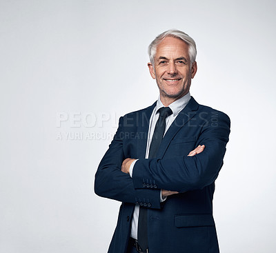 Buy stock photo Portrait of a mature businessman standing with his arms crossed against a grey background