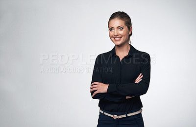 Buy stock photo Shot of a young businesswoman standing with her arms crossed against a grey background