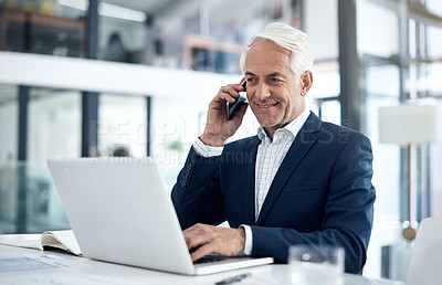 Buy stock photo Shot of a mature businessman talking on a cellphone while working on a laptop in an office