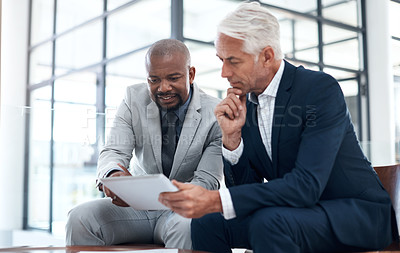 Buy stock photo Shot of two businessmen working together on a digital tablet in an office