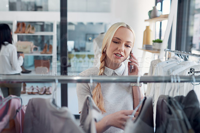 Buy stock photo Cropped shot of a young woman talking on her cellphone while out shopping for clothes